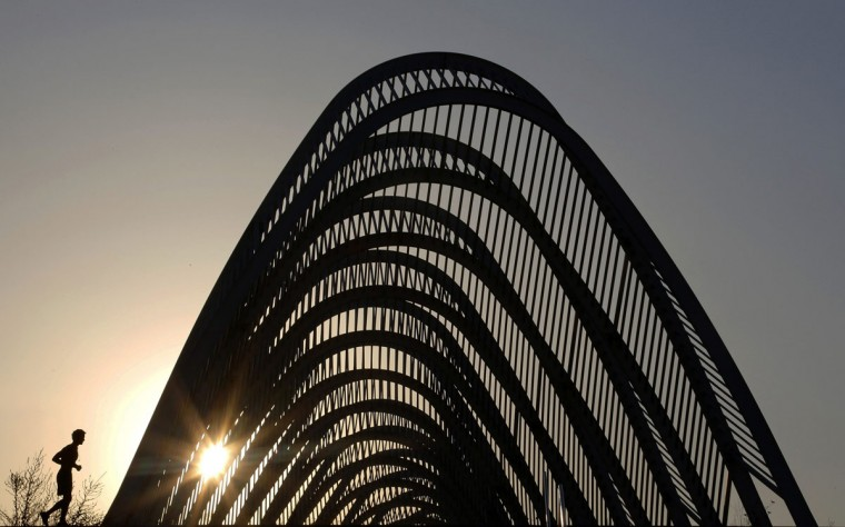 "A man jogs near the ""Agora"" structure at the Athens Olympic complex, at the site of the Athens 2004 Olympic Games. July 27, 2014. (Yannis Behrakis/Reuters)"