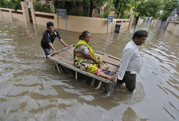 A woman is transported on a handcart through a flooded road after heavy monsoon rains in the western Indian city of Ahmedabad July 30, 2014. July, the second month of the monsoon season, usually gets the maximum rainfall, accounting for about a third of the seasonal downpour. (Amit Dave/Reuters photo)