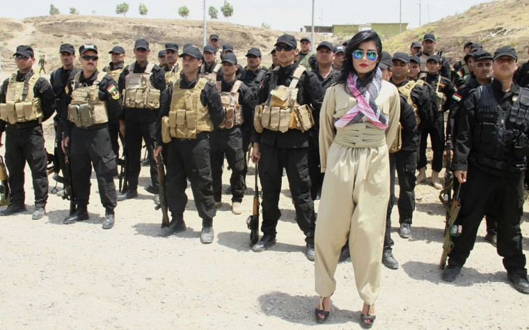 "Kurdish pop star Helly Luv poses in front of Kurdish Peshmerga troops at a base in Dohuk in this July 5, 2014 picture provided by Kawin Cihad Tahlavi and made available to Reuters on July 8, 2014. The singer says she will not be put off by death threats from Iraqi Islamist militants since release of her first music video but, drawing on its title, insists she will ""Risk It All"" to help a push for an independent Kurdistan. (REUTERS/Kawin Cihad Tahlavi/Handout via Reuters)"