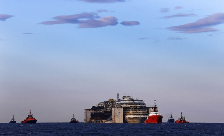 Tug boats tow the Costa Concordia ship as they arrive outside Genoa's port, in northern Italy, where the ship will be broken up for scrap, July 27, 2014. (Giampiero Sposito/Reuters)