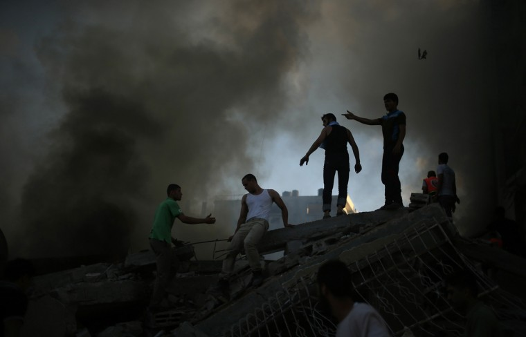 Palestinians try to extinguish a fire following what witnesses said was an Israeli air strike on a building in Gaza City July 24, 2014. Gazan authorities said Israeli forces shelled a shelter at a U.N.-run school on Thursday, killing at least 15 people as the Palestinian death toll in the conflict climbed over 750 and attempts at a truce remained elusive. The Israeli military said its troops were fighting gunmen from Hamas, which runs Gaza, in the area and that it was investigating the incident. Hamas fired rockets at Tel Aviv and said its gunmen carried out a lethal ambush on Israeli soldiers in north Gaza. (Suhaib Salem/Reuters)