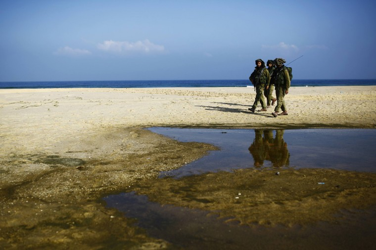 Israeli soldiers patrol on a beach outside the northern Gaza Strip July 24, 2014. Israel won a partial reprieve from the economic pain of its Gaza war on Thursday with the lifting of a U.S. ban on commercial flights to Tel Aviv, as fighting pushed the Palestinian death toll over 700. A truce between the Jewish state and Hamas-led Islamist guerrillas remained elusive despite intensive mediation bids. Palestinians said residents of two southern villages were trapped by days of tank shelling, with medics unable to evacuate wounded. U.N. agencies said more than 140,000 people had been displaced. Hamas fired rockets at Tel Aviv and said its gunmen carried out a lethal ambush on Israeli soldiers in north Gaza. (Amir Cohen/Reuters)