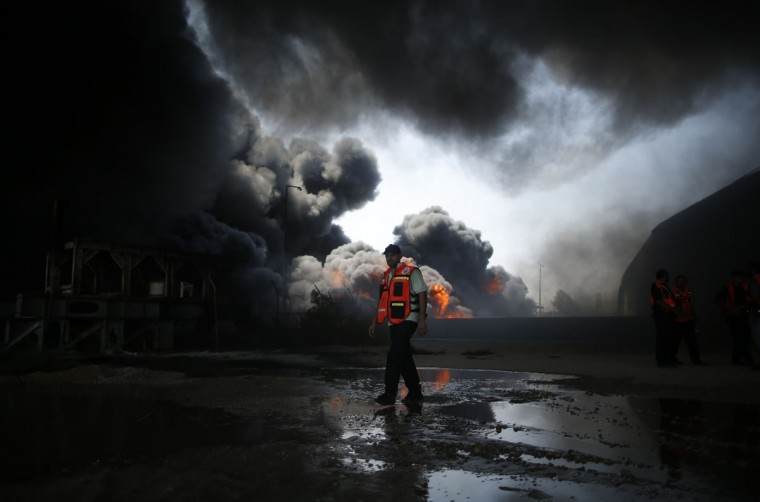 A Palestinian firefighter participates in efforts to put out a fire at Gaza's main power plant, which witnesses said was hit in Israeli shelling, in the central Gaza Strip July 29, 2014. Israeli tank fire hit the fuel depot of the Gaza Strip's only power plant on Tuesday, witnesses said, cutting electricity to Gaza City and many other parts of the Palestinian enclave of 1.8 million people.An Israeli military spokeswoman had no immediate comment and said she was checking the report. Israel launched its Gaza offensive on July 8, saying its aim was to halt rocket attacks by Hamas and its allies. (REUTERS/Mohammed Salem)