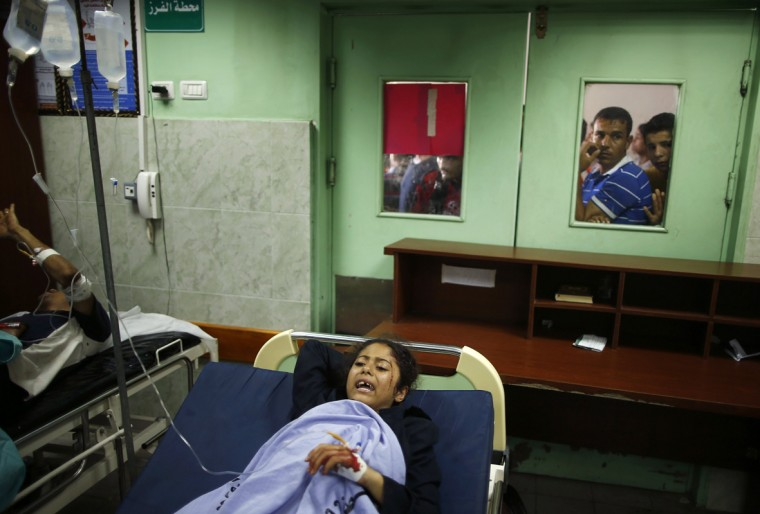 A Palestinian girl, whom medics said was wounded in Israeli shelling at a U.N-run school sheltering Palestinian refugees, lies on a bed at a hospital in the northern Gaza Strip July 24, 2014. At least 15 people were killed and many wounded on Thursday when Israeli forces shelled a U.N.-run school sheltering Palestinian refugees in northern Gaza, said a spokesman for the Gaza health ministry, Ashraf al-Qidra. Chris Gunness, spokesman for the main U.N. agency in Gaza UNRWA, confirmed the strike and criticised Israel. The Israel army had no immediate comment on the reports. Hamas fired rockets at Tel Aviv and said its gunmen carried out a lethal ambush on Israeli soldiers in north Gaza. (Mohammed Salem/Reuters)