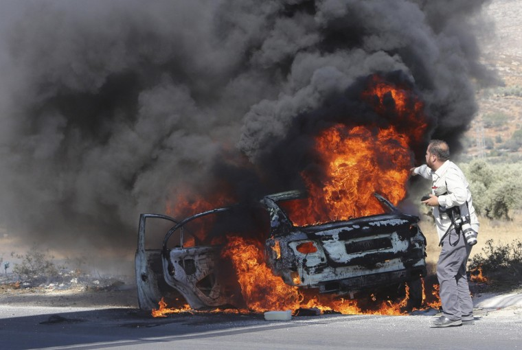 AFP photographer Jaafar Ishtayeh looks at his burning car after it was hit by tear gas canisters fired by Israeli soldiers, during a protest by Palestinians against Israeli air strikes in Gaza strip, at Hawara checkpoint near the West Bank city of Nablus. Ishtayeh, a Palestinian, was at the scene to provide coverage of the protest. (Abed Omar Qusini/Reuters)