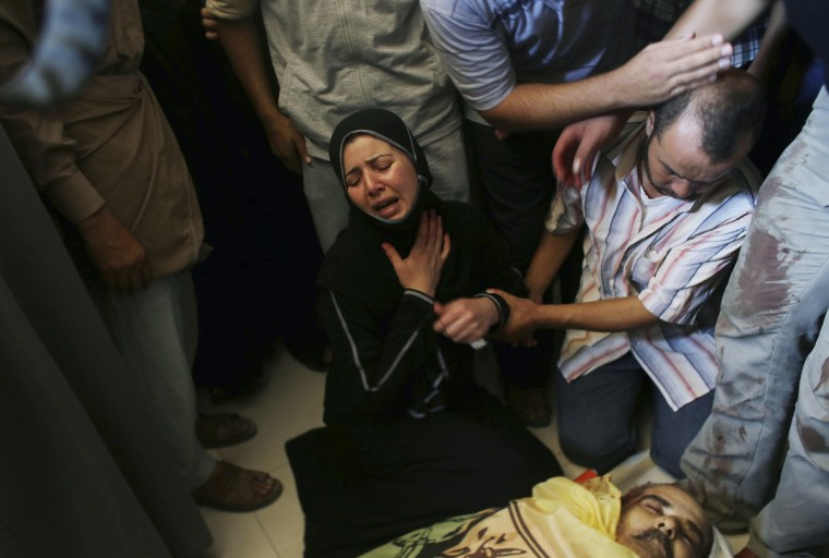 Palestinian daughter of Tawfiq al-Aga, who medics said was killed in Israeli shelling, mourns next to her father body during his funeral in Khan Younis in the southern Gaza Strip July 23, 2014. Israeli forces pounded Gaza on Wednesday, meeting stiff resistance from Hamas Islamists and sending thousands of residents fleeing, as U.S. Secretary of State John Kerry said on a visit to Israel ceasefire talks had made some progress. Israel launched its offensive on July 8 to halt missile salvoes by Hamas and its allies, struggling under the weight of an Israeli-Egyptian economic blockade and angered by a crackdown on their supporters in the nearby occupied West Bank. (Ibraheem Abu Mustafa/Reuters)