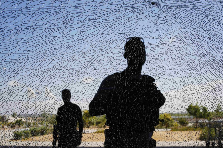 Israeli security personnel look at a window damaged by shrapnel after a short-range rocket landed on Tuesday near the Erez crossing. An Israeli civilian was killed by the rocket fired from the Gaza Strip on Tuesday, the military said, the first Israeli fatality in more than a week of fighting with Palestinian militants. The Islamist group Hamas that rules Gaza claimed responsibility for launching the short-range rocket that struck an area along the border with Gaza. (Finbarr O'Reilly/Reuters)