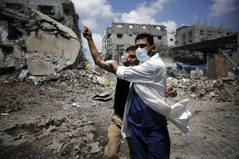 A medic helps a Palestinian in the Shejaia neighborhood, which was heavily shelled by Israel during fighting, in Gaza City July 20, 2014. At least 50 Palestinians were killed on Sunday by Israeli shelling in the Gaza neighborhood, where bodies were strewn in the street and thousands fled for shelter to a hospital packed with wounded, witnesses and health officials said. Militants kept up their rocket fire on Israel, with no sign of a diplomatic breakthrough toward a ceasefire in sight. (Finbarr O'Reilly/Reuters)