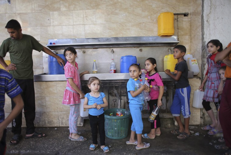 Palestinian children fill bottles and containers with water from a public tap in Rafah in the southern Gaza Strip July 17, 2014. Palestinians rushed to shops and banks on Thursday during a five-hour humanitarian ceasefire that largely held, and an Israeli official said Egypt had proposed a permanent truce that would start on Friday. Gaza health officials say at least 224 Palestinians, mostly civilians, have been killed in 10 days of warfare between the Islamist Hamas rulers of Gaza and Israel. In Israel, one civilian has been killed by fire from Gaza, where the Israeli military says more than 1,300 rockets have been launched into the Jewish state. (Ibraheem Abu Mustafa/Reuters)