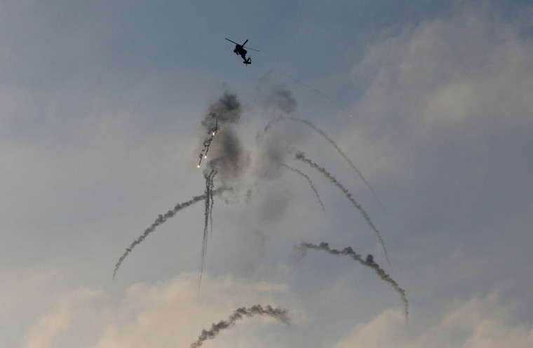An Israeli Apache helicopter fires flares above Israel near the border with northern Gaza July 20, 2014. Israel said on Sunday it had expanded its ground offensive in Gaza and militants kept up rocket fire into the Jewish state with no sign of a diplomatic breakthrough to end the worst fighting between Israel and Hamas in two years. (Baz Ratner/Reuters)