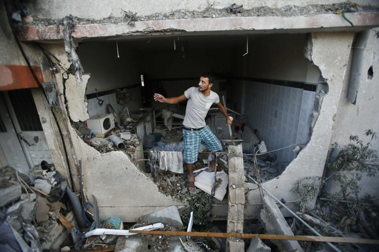A Palestinian man inspects a house which police said was damaged in an Israeli air strike, in Gaza City July 21, 2014. Israeli tanks shelled militant targets in the Gaza Strip on Monday and a woman died in an air strike after the bloodiest day of a nearly two-week military offensive that showed no signs of abating, despite global calls for a truce. Palestinian health officials said the death toll since July 8 had reached 447, including many civilians, with a woman killed in the predawn strike in Beit Hanoun and 12 more bodies recovered from the embattled Shejaia neighborhood where the number of fatalities rose to 72 from Sunday's fighting. Israel's army said it had been targeting militants from Gaza's dominant Hamas group, charging that they fired rockets from Shejaia and built tunnels and command centres there. The army said it had warned civilians to leave two days earlier. (REUTERS/Suhaib Salem)