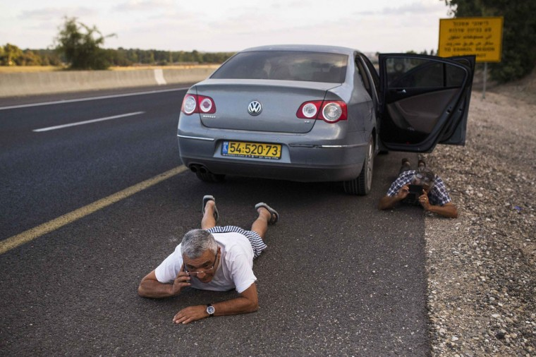 Israelis take cover on the side of a road as a siren sounds warning of incoming rockets outside the northern Gaza Strip July 15, 2014. Israel resumed air strikes in the Gaza Strip on Tuesday after agreeing to an Egyptian-proposed ceasefire deal that failed to get Hamas militants to halt rocket attacks. The week-old conflict seemed to be at a turning point, with Hamas defying Arab and Western calls to cease fire and Israel threatening to step up an offensive that could include an invasion of the densely populated enclave of 1.8 million. (REUTERS/Amir Cohen)