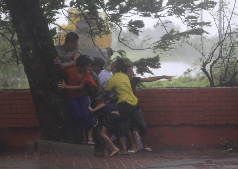 People take cover under a tree after strong winds brought by Typhoon Rammasun, locally called Glenda, battered the capital, metro Manila. Philippine authorities evacuated almost 150,000 people from their homes and shuttered financial markets, government offices, businesses and schools on Wednesday as typhoon Rammasun gathered strength and hit the capital, Manila. (Romeo Ranoco/Reuters)