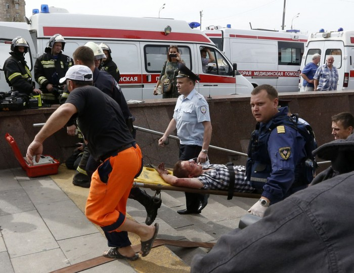 Members of the emergency services carry an injured passenger outside a metro station following an accident on the subway in Moscow July 15, 2014. Nineteen people were killed on Tuesday and up to 120 injured when a Moscow underground train derailed between two stations during the morning rush hour, the Emergencies Ministry said. (REUTERS/Sergei Karpukhin)