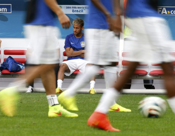Brazil's Neymar watches his teammates warm up hefore the 2014 World Cup third-place playoff between Brazil and the Netherlands at the Brasilia national stadium in Brasilia July 12, 2014. (Ueslei Marcelino/Reuters)