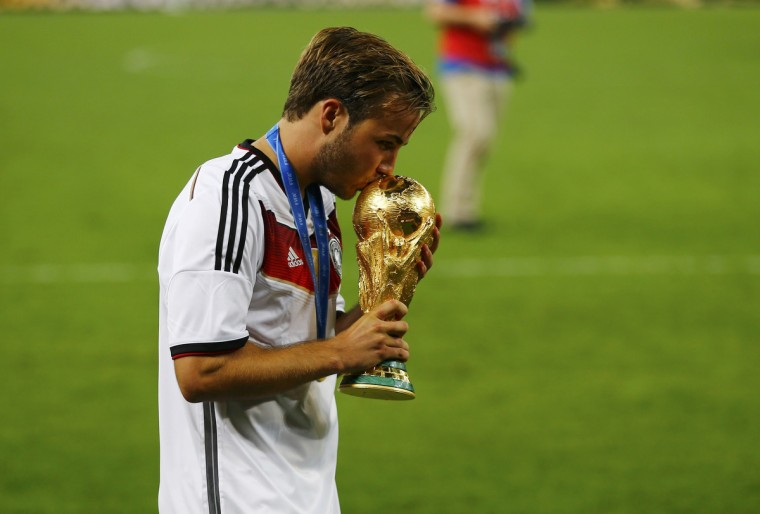 Germany's Mario Goetze kisses the World Cup trophy as he celebrates their 2014 World Cup final win against Argentina at the Maracana stadium in Rio de Janeiro July 13, 2014. (Damir Sagolj/Reuters)