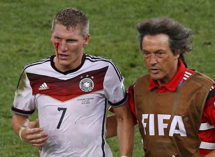 Germany's Bastian Schweinsteiger (L) leaves the pitch after he was injured during extra time in their 2014 World Cup final against Argentina at the Maracana stadium in Rio de Janeiro July 13, 2014. (David Gray/Reuters)