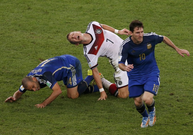 Germany's Bastian Schweinsteiger reacts as he falls on the pitch past Argentina's Javier Mascherano (R) and Lionel Messi (R) during extra time in their 2014 World Cup final at the Maracana stadium in Rio de Janeiro July 13, 2014. (David Gray/Reuters)