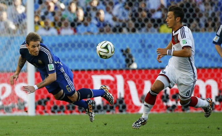 Argentina's Lucas Biglia (L) fights for the ball with Germany's Mesut Ozil during their 2014 World Cup final at the Maracana stadium in Rio de Janeiro July 13, 2014. (Damir Sagolj/Reuters)