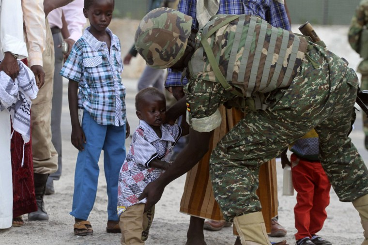 A soldier serving in the African Union Mission in Somalia (AMISOM) frisks a Muslim child before allowing entry to attend Eid al-Fitr prayers to mark end of the fasting month of Ramadan, at a Mosque in Somalia's capital Mogadishu, July 28, 2014. (REUTERS/Ismail Taxta)