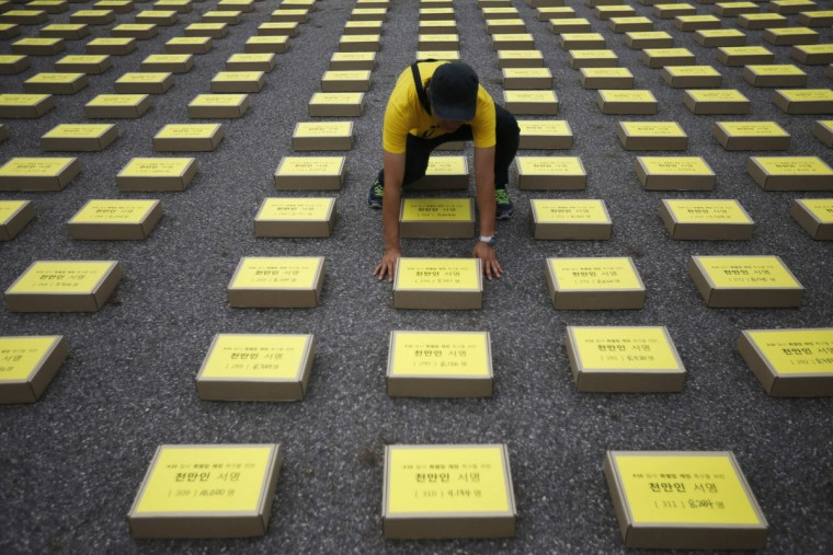 "A man arranges a box containing signatures of South Koreans petitioning for the enactment of a special law after the mid-April Sewol ferry disaster, at Yeouido Park in Seoul July 15, 2014. The petition is demanding the government for an impartial investigation into the disaster, as well as just punishment for those responsible and measures to prevent its recurrence, according to local media. Many of the 250 children who drowned when the ferry sank would have survived if the crew had issued a simple order to evacuate to emergency decks just outside their cabins, a prosecutor said on July 8. The words on the box read, ""10,000,000 citizens' signatures demanding Special Law for April 16 Sewol Ferry Tragedy"". (REUTERS/Kim Hong-Ji)"