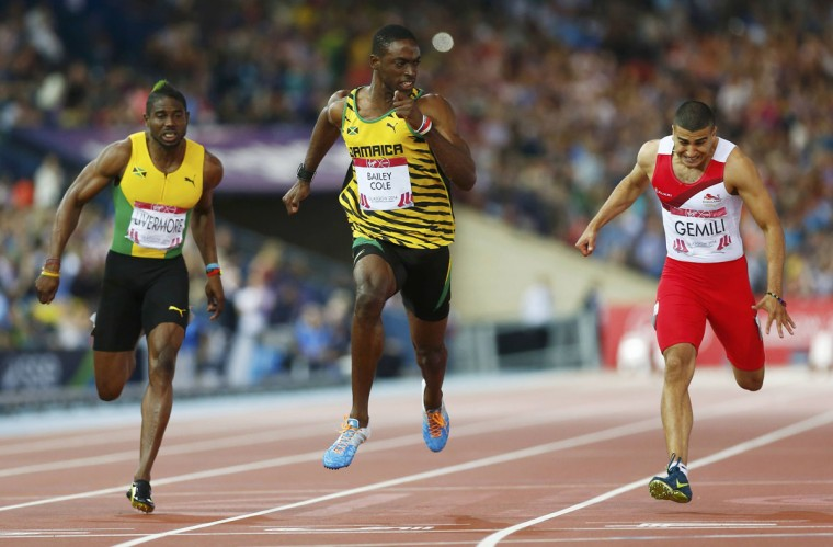Kemar Bailey-Cole (C) of Jamaica finishes first place ahead of Adam Gemili (R) of England, and Jason Livermore of Jamaica during the men's 100m final at the 2014 Commonwealth Games in Glasgow, Scotland, July 28, 2014. (REUTERS/Andrew Winning)