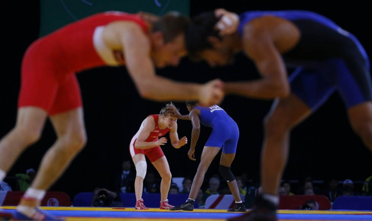Sasha Madyarchyk of England (front Left) grapples with Bajrang Bajrang of India (front Right) during their men's freestyle 61kg wrestling match, as Jill Gallays of Canada (back Left) tussles with Odunayo Adekuoroye of Nigeria during their women's freestyle 53kg quarter-final at the 2014 Commonwealth Games in Glasgow, Scotland, July 30, 2014. (Phil Noble/Reuters photo)