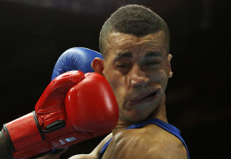 Kenya's Denis Okoth lands a punch on England's Samuel Maxwell during their men's Light Welterweight boxing fight at the Commonwealth Games in Glasgow, Scotland, July 27, 2014. (Jim Young/Reuters)