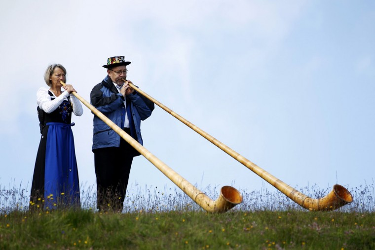 Alphorn blowers perform an ensemble piece on the last day of the International Alphorn Festival on Lac de Tracouet near the village of Nendaz, July 27, 2014. About 150 alphorn blowers took part in the contest this year. (Pierre Albouy/Reuters)