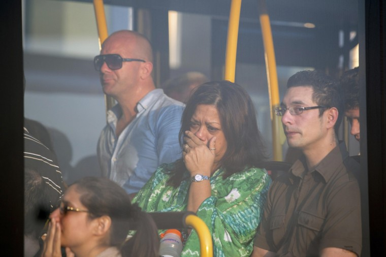 Family members of passengers on Malaysia Airlines flight MH-17 react on a bus bringing them to a separate area at Schiphol Airport July 17, 2014. The Malaysian airliner was brought down over eastern Ukraine on Thursday, killing all 295 people aboard and sharply raising the stakes in a conflict between Kiev and pro-Moscow rebels in which Russia and the West back opposing sides. (Cris Toala Olivares/Reuters)