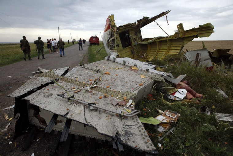 People stand near part of the wreckage of a Malaysia Airlines Boeing 777 plane after it crashed near the settlement of Grabovo in the Donetsk region, July 17, 2014. The Malaysian airliner Flight MH-17 was brought down over eastern Ukraine on Thursday, killing all 295 people aboard and sharply raising stakes in a conflict between Kiev and pro-Moscow rebels in which Russia and the West back opposing sides. (Maxim Zmeyev/Reuters)