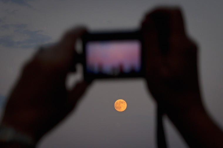 A woman takes a photo of the moon one day ahead of the Supermoon phenomenon from a bridge over 42nd St. in the Manhattan borough of New York July 11, 2014. Occurring when a full moon or new moon coincides with the closest approach the moon makes to the Earth, the Supermoon results in a larger-than-usual appearance of the lunar disk. REUTERS/Carlo Allegri