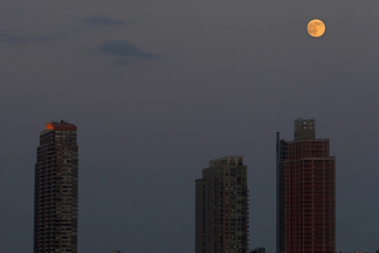 The moon is pictured one day ahead of the Supermoon phenomenon as it rises over buildings in Long Island City, seen from a bridge over 42nd St. in the Manhattan borough of New York July 11, 2014. Occurring when a full moon or new moon coincides with the closest approach the moon makes to the Earth, the Supermoon results in a larger-than-usual appearance of the lunar disk. REUTERS/Carlo Allegri