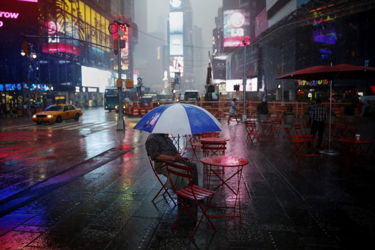 A man sits with an umbrella during a rainstorm at Times Square in New York July 15, 2014. (REUTERS/Shannon Stapleton)