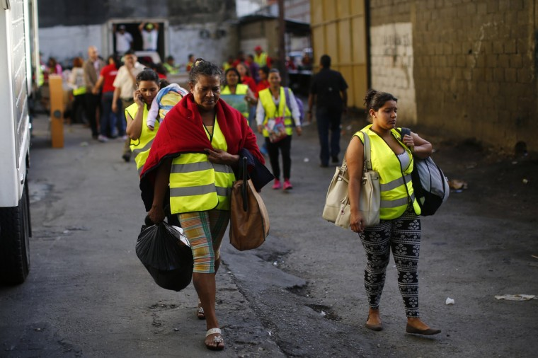 "Evicted residents of Tower of David walks out the building to a bus which will transport them to their new house in Caracas July 22, 2014. Venezuelan soldiers and officials began moving hundreds of families on Tuesday out of the half-built 45-story skyscraper that dominates the Caracas skyline and is thought to be the tallest slum in the world. The mass eviction from the ""Tower of David"", originally intended to be a bank center but abandoned since 1994 and later home to some 3,000 needy Venezuelans, proceeded peacefully. (Jorge Silva/Reuters)"