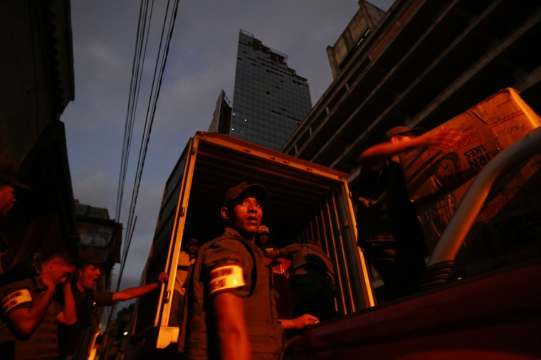 "Venezuelan national guard carry into a truck the belongings of evicted Tower of David (in the background) residents in Caracas July 22, 2014. Venezuelan soldiers and officials began moving hundreds of families on Tuesday out of a half-built 45-story skyscraper that dominates the Caracas skyline and is thought to be the tallest slum in the world. The mass eviction from the ""Tower of David"", originally intended to be a bank center but abandoned since 1994 and later home to some 3,000 needy Venezuelans, proceeded peacefully. (Jorge Silva/Reuters)"