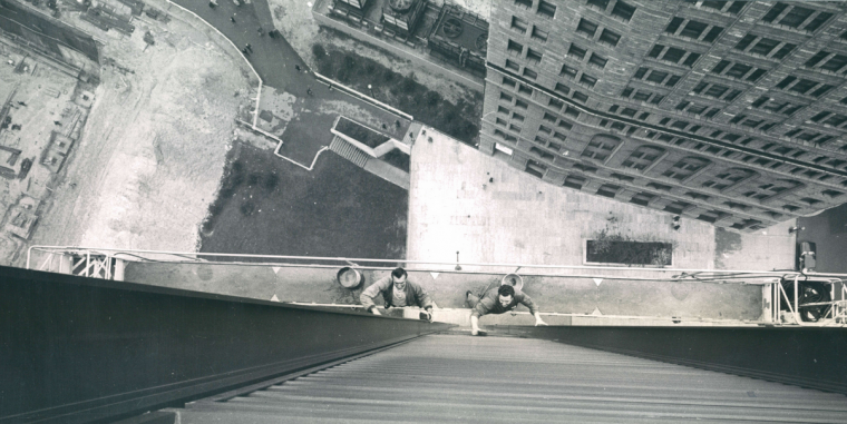"""June 4, 1964: Window washers Nick Murdich and Bob Cave, seen from the One Charles Center window, lean in at the 22nd floor. At the end of the scaffolding, railed enclosures called """"buckets"""" hold motors, cables, and electric cord. Rollers fit behind beams to hold scaffold close to the building. (Ellis Malashuk)"""