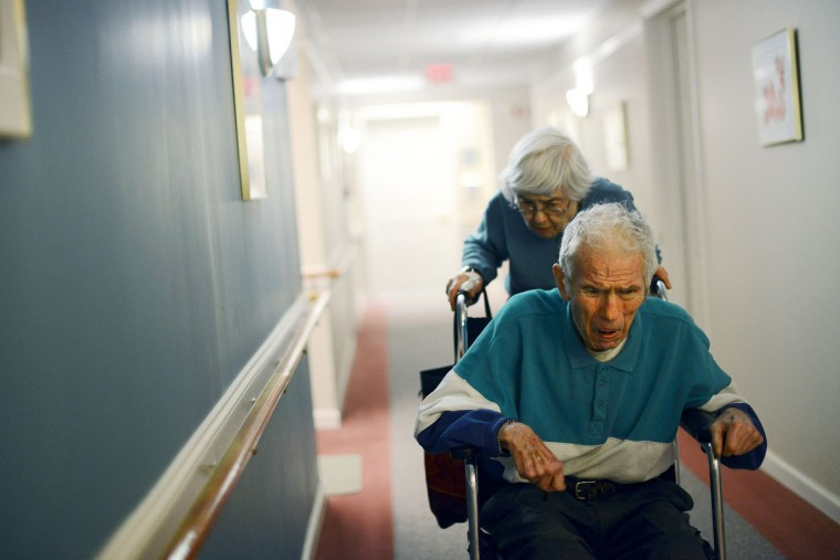 "Eleanor Barnard pushes Roger Barnard in the hallway of Longview. If Roger is unable to support himself it's hard for Eleanor to help. ""If he ends up on the floor I can't pick him up,"" Eleanor said. Rachel Woolf/Baltimore Sun"