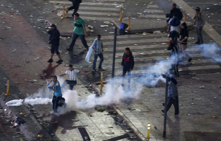 Argentina's fans run away from tear gas as they clash with riot police in Buenos Aires after Argentina lost to Germany in the 2014 World Cup final. (REUTERS/Ivan Alvarado)