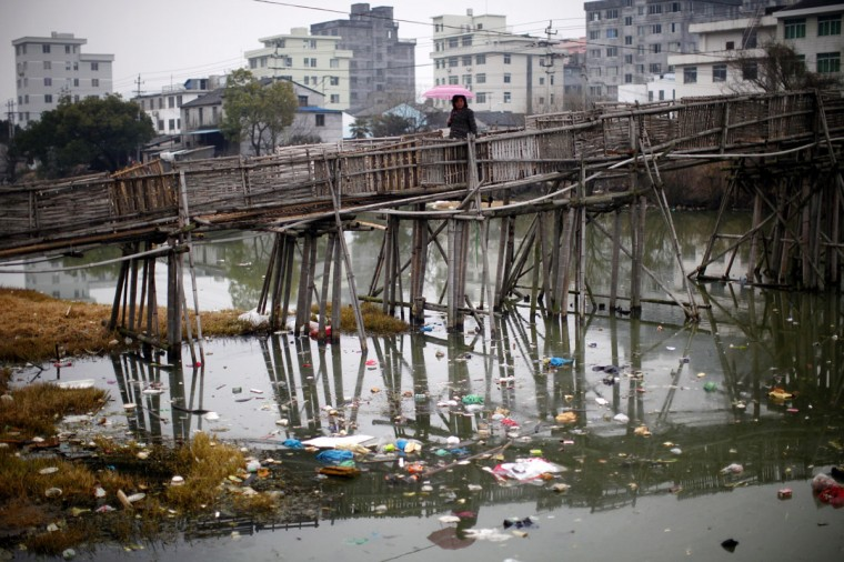 A woman walks on a bridge over a polluted river at a suburban area of Wenzhou, in Zhejiang province February 18, 2011. (REUTERS/Carlos Barria)