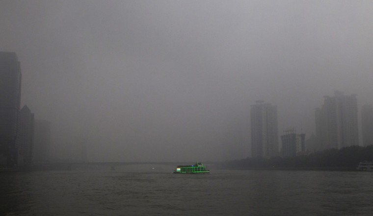 A tourist boat, decorated with green lights, travels on the Pearl River amid heavy haze in Guangzhou, Guangdong province March 3, 2014. China's environment ministry has vowed to 'harshly punish' factories and power plants that contributed to a hazardous smog which enveloped much of Northern China, official state media reported. (REUTERS/Alex Lee)