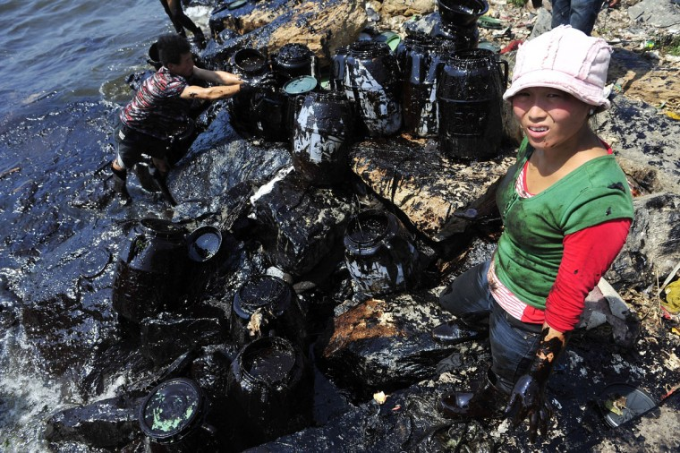 Fishermen clean up oil at an oil spill site near Dalian Port, Liaoning province July 27, 2010. (REUTERS/Stringer)