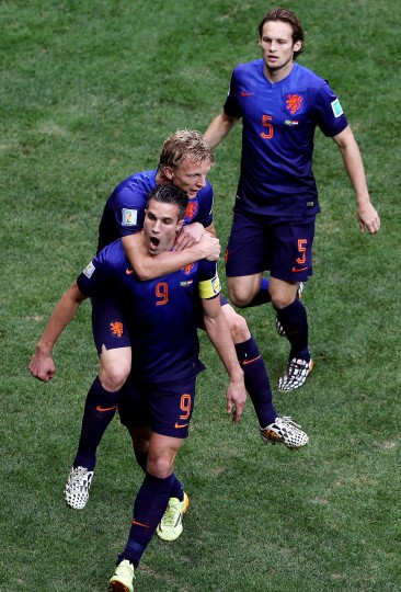 Robin van Persie of the Netherlands celebrates scoring his team's first goal on a penalty kick with Dirk Kuyt and Daley Blind during the 2014 FIFA World Cup Brazil Third Place Playoff match between Brazil and the Netherlands at Estadio Nacional in Brasilia, Brazil. (Celso Junior/Getty Images)