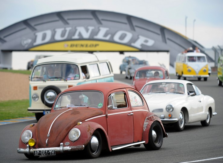 "People parade with their Volkswagens during the ""Super VW Festival"" on Le Mans' circuit, western France. The festival, which runs from July 25 to 27, gathers nearly 1200 aircooled Volkswagen cars including the models Beetle, Transporter, and Dune Buggy. (Jean-Francois Monier/AFP-Getty Images)"