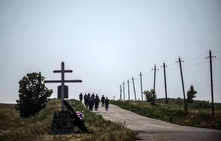 Members of the Ukrainian State Emergency Service walk near the crash site of the Malaysia Airlines Flight MH17 near the village of Hrabove (Grabovo), in the Donetsk region. Ukraine sought on July 25 to avoid a political crisis after the shock resignation of its prime minister, as fighting between the army and rebels close to the Malaysian airliner crash site claimed over a dozen more lives. Dutch and Australian forces were being readied on July 26 for possible deployment to secure the rebel-held crash site of the Malaysia Airlines flight MH17 in east Ukraine where many victims' remains still lie nine days after the disaster claimed 298 lives. (Buleny Kilic/AFP-Getty Images)