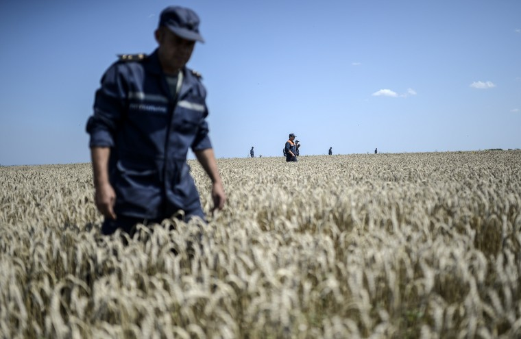 Members of the Ukrainian State Emergency Service search for bodies in a field near the crash site of the Malaysia Airlines Flight MH17 near the village of Hrabove (Grabovo), in Donetsk region. Ukraine sought on July 25 to avoid a political crisis after the shock resignation of its prime minister, as fighting between the army and rebels close to the Malaysian airliner crash site claimed over a dozen more lives. The Netherlands and Australia, the two countries that lost the most citizens when the Malaysia Airlines Boeing 777 was shot down, are seeking a mandate to deploy troops on the ground, possibly through a United Nations Security Council resolution. (Bulent Kilic/AFP-Getty Images)