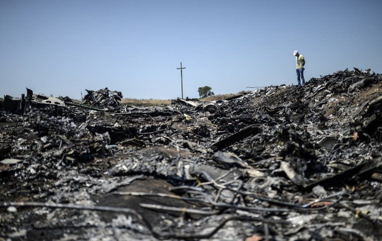 man stands at the crash site of the Malaysia Airlines Flight MH17, near the village of Hrabove (Grabove), in the Donetsk region. Ukraine sought on July 25 to avoid a political crisis after the shock resignation of its prime minister, as fighting between the army and rebels close to the Malaysian airliner crash site claimed over a dozen more lives. Dutch and Australian forces were being readied on July 26 for possible deployment to secure the rebel-held crash site of the Malaysia Airlines flight MH17 in east Ukraine where many victims' remains still lie nine days after the disaster claimed 298 lives. (Bulent Kilic/AFP-Getty Images)