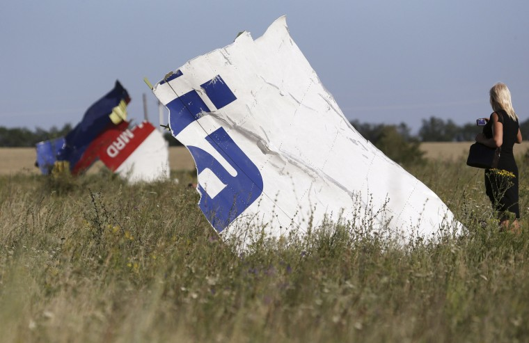 A woman takes a photograph of wreckage at the crash site of Malaysia Airlines Flight MH17 near the village of Hrabove (Grabovo), Donetsk region. Nearly 300 people, 193 of them Dutch citizens, were killed when the Malaysia Airlines plane en route from Amsterdam to Kuala Lumpur was brought down in eastern Ukraine, where separatists are battling government forces, on July 17. (Sergei Karpukhin/Reuters)