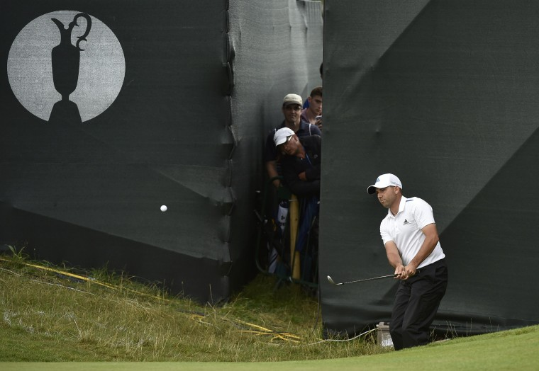 Spectators peer between grandstands as Sergio Garcia of Spain chips onto the 15th green during the third round of the British Open Championship at the Royal Liverpool Golf Club in Hoylake, northern England. (Toby Melville/Reuters)