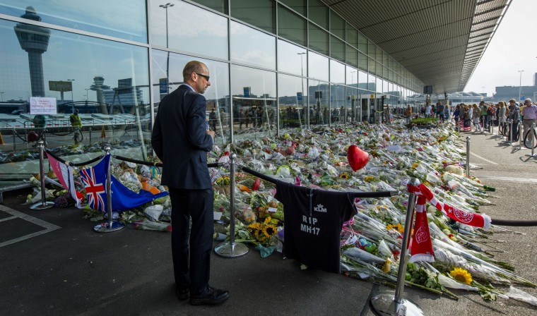 A passenger watches flowers layed in commemoration of the victims of the Malaysia Airlines flight MH17, at Schiphol Airport, near Amsterdam.. More than a week after Malaysia Airlines flight MH17 came down in rebel-held eastern Ukraine human remains are still at the crash site, Australian Prime Minister Tony Abbott said on July 26. (Bart Maat/AFP-Getty Images)